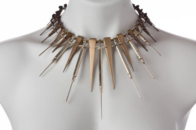 Cast silver and bronze spikes and syringes on a silver rod.